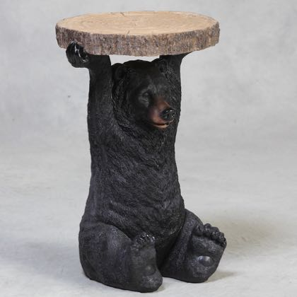 black bear side table has a bear holding a slice of tree trunk above his head that is the surface of the table. Measures 52 x 36 x 36cm