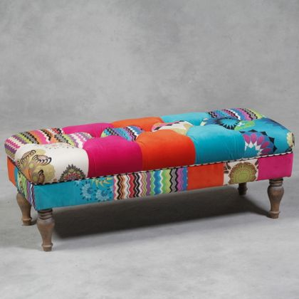 multicoloured patchwork wide stool bench is button upholstered in a luxurious feeling material that is mainly orange, pink and turquoise in colour. Measures 110 x 45 x 39cm