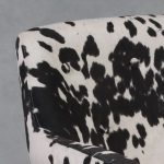 detail of the faux cream and black cowhide chair