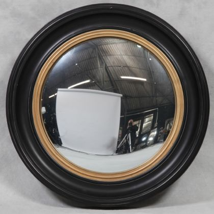 large black convex mirror is a huge round mirror that has a black and gold painted wooden frame and a convex mirror