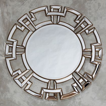 gold round mirror with gold edging to the art deco aztec styling